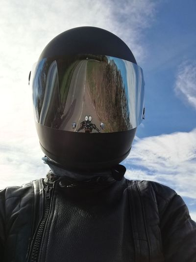 Man Wearing Helmet With Reflection Of Motor Cycle Against Sky