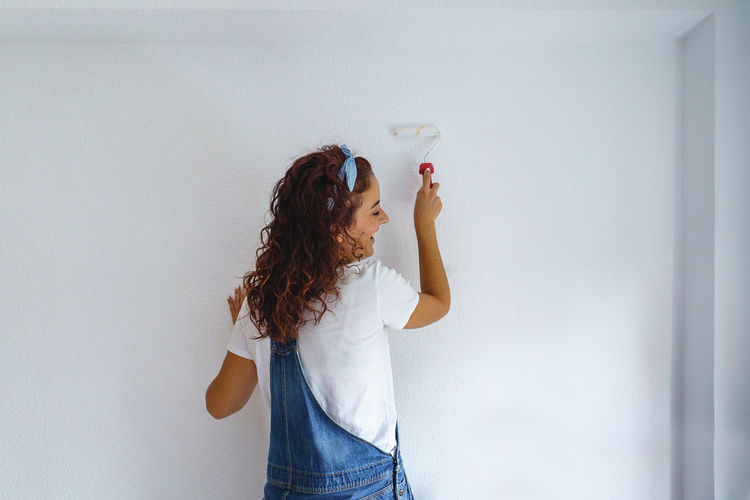 Rear view of woman painting wall at home
