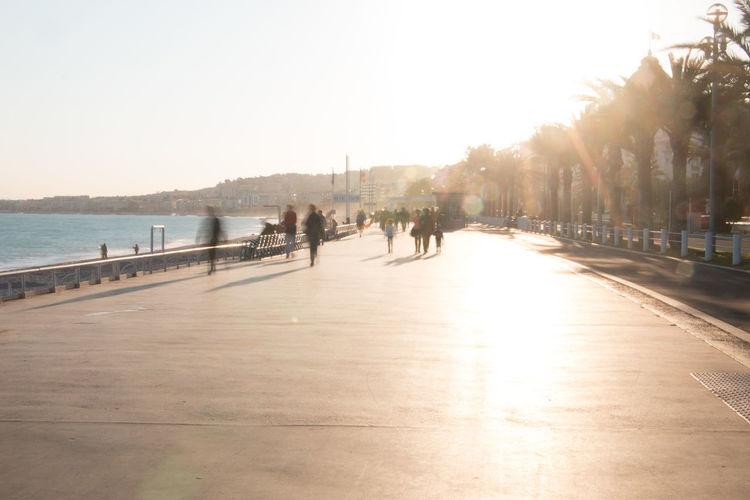 People walking on footpath by sea against clear sky
