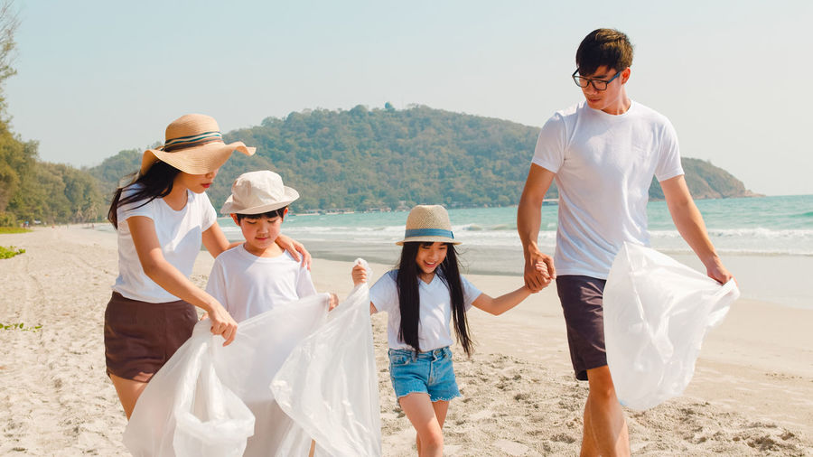Family with plastic bags walking at beach