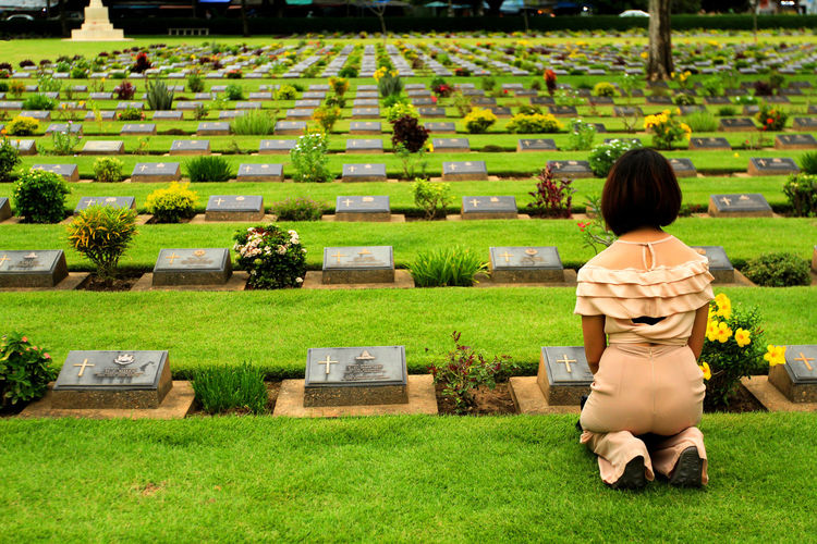Rear view of woman with flowers on grass