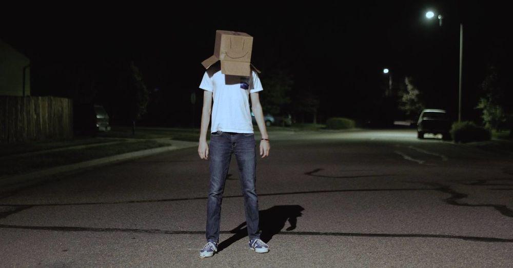 Rear view of man walking on road at night