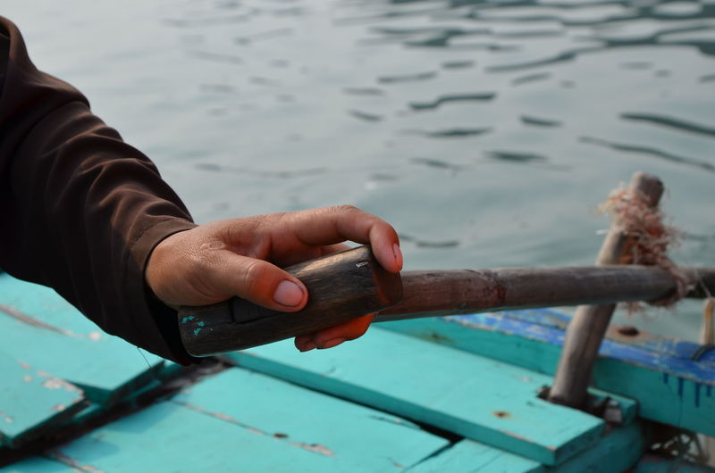 Cropped hand holding oar on boat in sea
