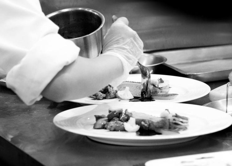 Midsection of person preparing food in plate on table
