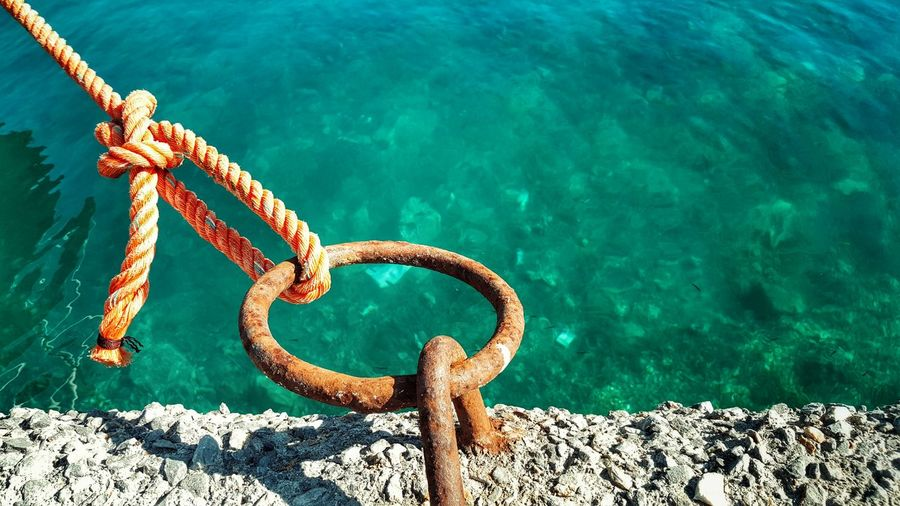 Rope tied on rusty mooring ring at harbor