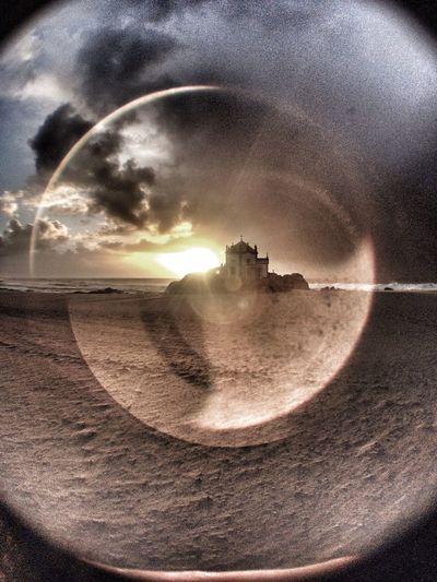 Sun shining through clouds over sea