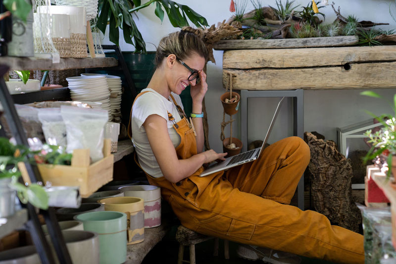 Side view of smiling florist video calling on laptop while sitting at shop