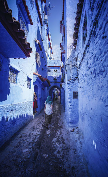 """""""The Blue City"""" - Chefchaouen, Morocco. Chefchaouen Chefchaouen Medina Medina Morocco MoroccoTrip EyeEmNewHere a new beginning Digital Nomad Travel Travel Destinations Traveling Travel Photography Photography Blue City Alley Maze Arabic Moroccans Tourism Tourist Attraction  Tourist Destination Architecture Built Structure Building Exterior Real People Day Building Winter Full Length Cold Temperature Walking Snow Men The Way Forward People Nature Direction Residential District Outdoors"""