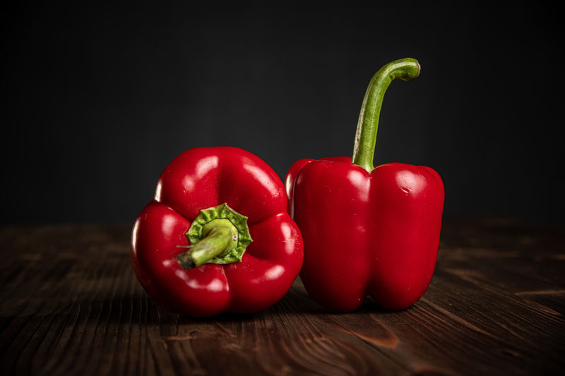 Close-up of red bell peppers on table against black background