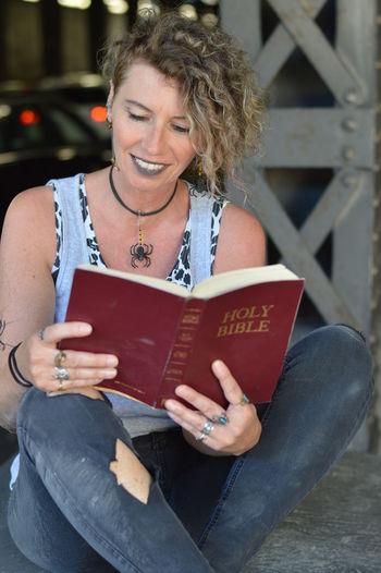 Smiling mature woman reading bible