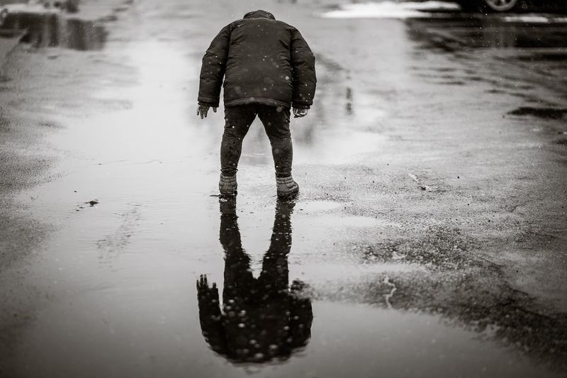 Rear view of boy standing on wet footpath during winter