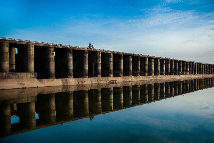 Bridge reflecting on lake against sky