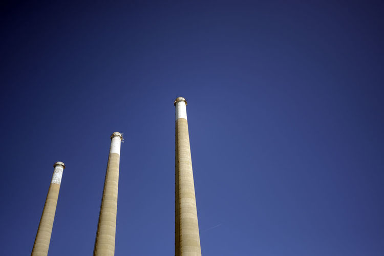 Air Pollution Blue Chimney Clear Sky Day Emitting Factory Fumes Industry Low Angle View No People Outdoors Pollution Power Station Sky Smoke - Physical Structure Smoke Stack Vapor Trail