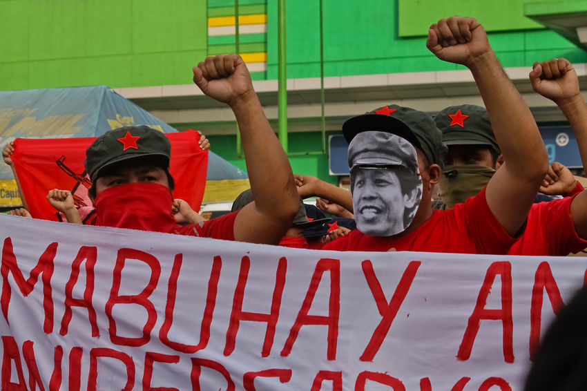 Supporters of the New People's Army (NPA) stage a lightning rally in front of a public market in Calamba City, Laguna. The NPA, the armed wing of the Communist Party of the Philippines (CPP), is celebrating its 48th anniversary today, March 29, 2017. A unilateral ceasefire is set to be declared by the CPP not later than March 31, ahead of the resumption of peace talks between the National Democratic Front of the Philippines (NDFP) and the government in April. KIMMY BARAOIDAN Adult Adults Only Arms Raised Fists Group Of People People Protest Protesters Red