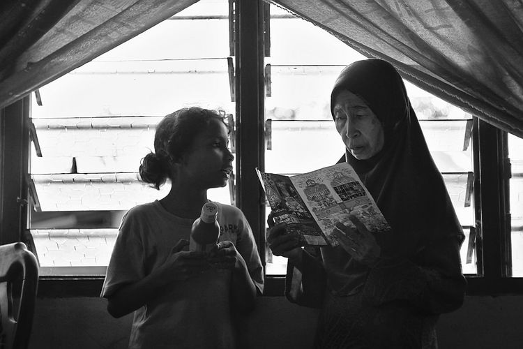 Girl with grandmother against window at home