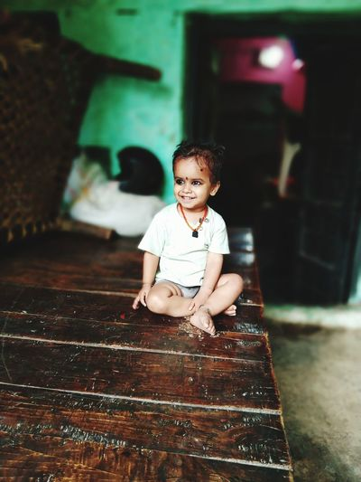 Portrait of a smiling girl sitting on floor at home