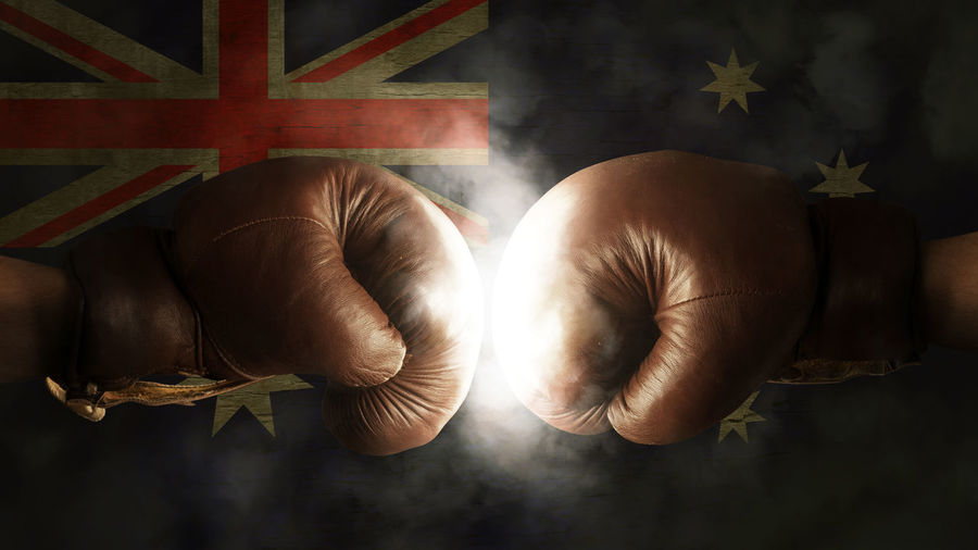 Cropped image of boxers fighting against illuminated australian flag