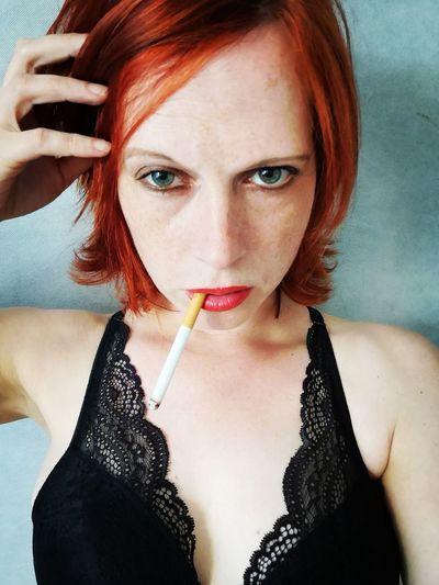 Close-up portrait of redhead woman smoking cigarette