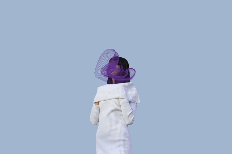 Woman with purple scarf standing against gray background
