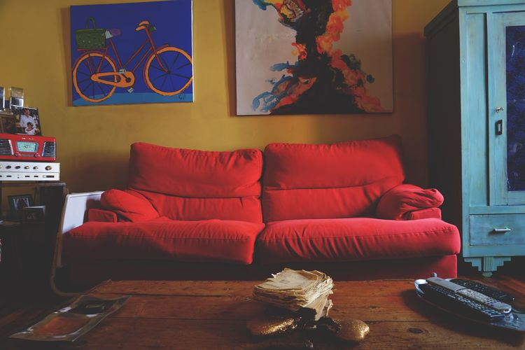 Empty sofa by papers and remote control on tables at home