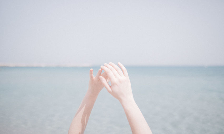 Cropped hands against sea at beach during summer
