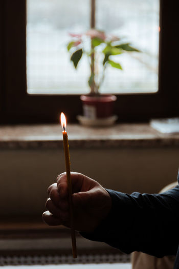 Cropped hand of person holding candle at home