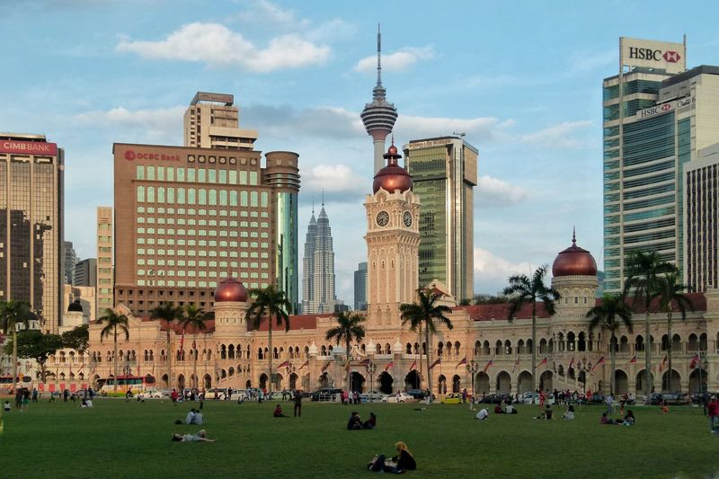 People at lawn by sultan abdul samad building with skyscrapers in city