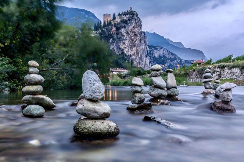 Stack of stones in river against sky