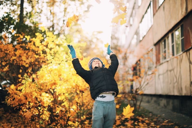 Cute boy throwing dry leaves during autumn