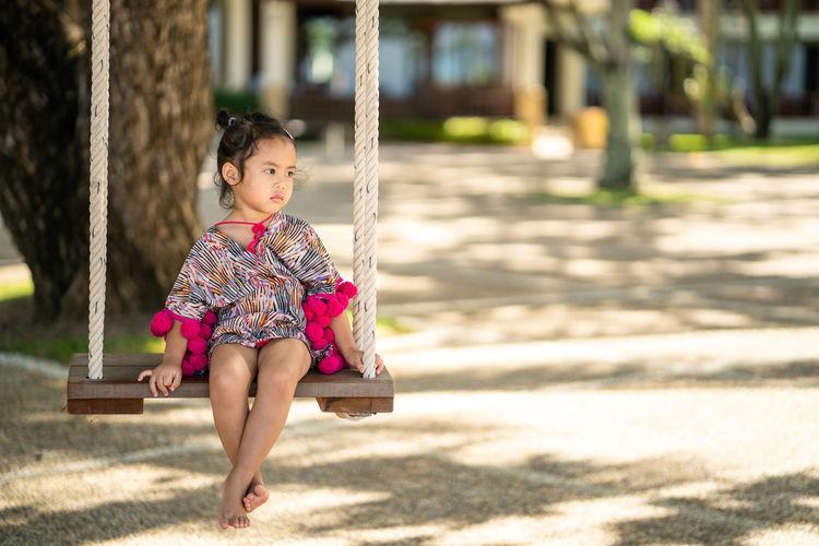 Full length of girl sitting on playground