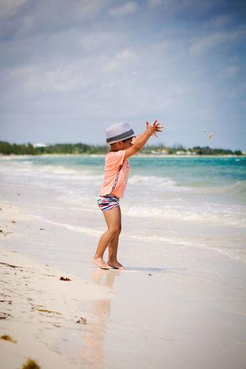 Full length of woman with arms raised on beach against sky