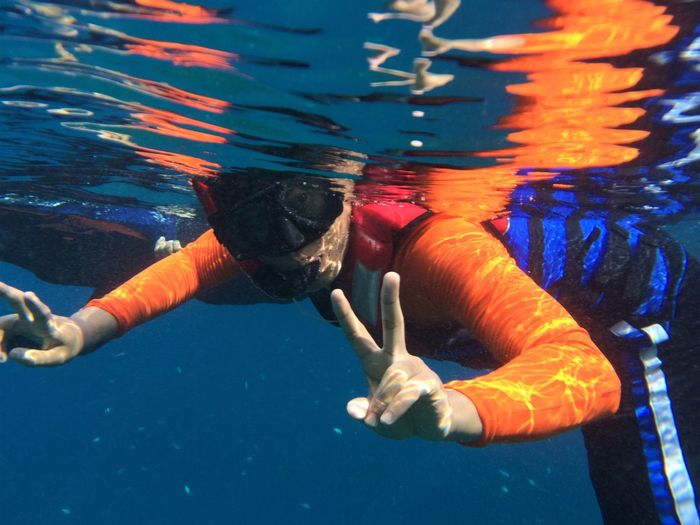 Portrait Of Young Man Gesturing Peace Sign While Snorkeling In Sea