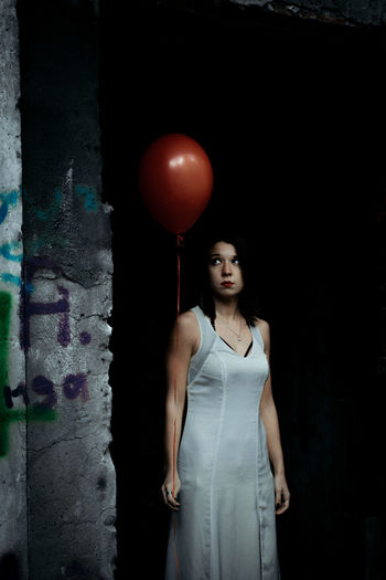 Woman holding helium balloon while standing by wall