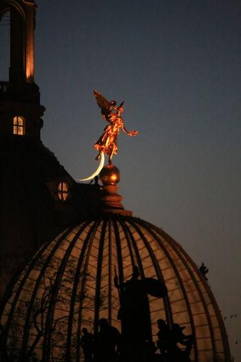 Statue of illuminated building against sky