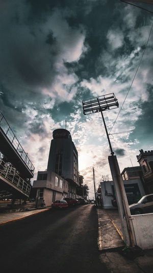 Low angle view of street amidst buildings against sky