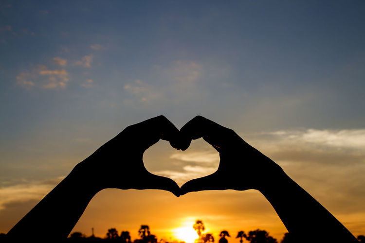 Valentine's day concept, Silhouette hand in heart shape with sunset Romantic Valentine's Day  Body Part Cloud - Sky Hand Heart Heart Shape Human Body Part Lifestyles Love Nature Orange Color Outdoors Silhouette Sky Summer Sun Sunset