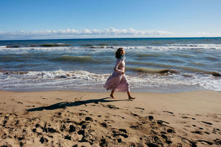 Adult Barefoot Beach Beauty In Nature Day Full Length Horizon Over Water Leisure Activity Motion Nature One Person One Woman Only Only Women Outdoors Rear View Sand Scenics Sea Shadow Sky Surf Vacations Walking Wave Women