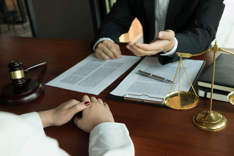 Midsection of lawyer and woman discussing over papers on table