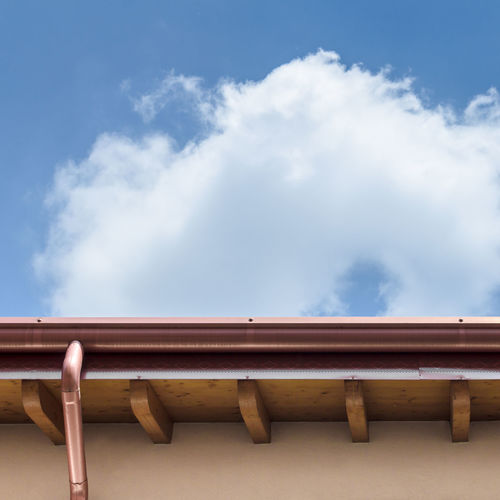 Low angle view of roof against cloudy sky