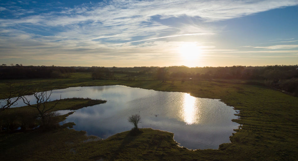 Aerial drone flight over a lake at sunset in the winter Aerial View Blue Sky With Clouds Bushes Dronephotography Lake View Leicestershire Night Sunset Trees And Nature Water Reflections Winter