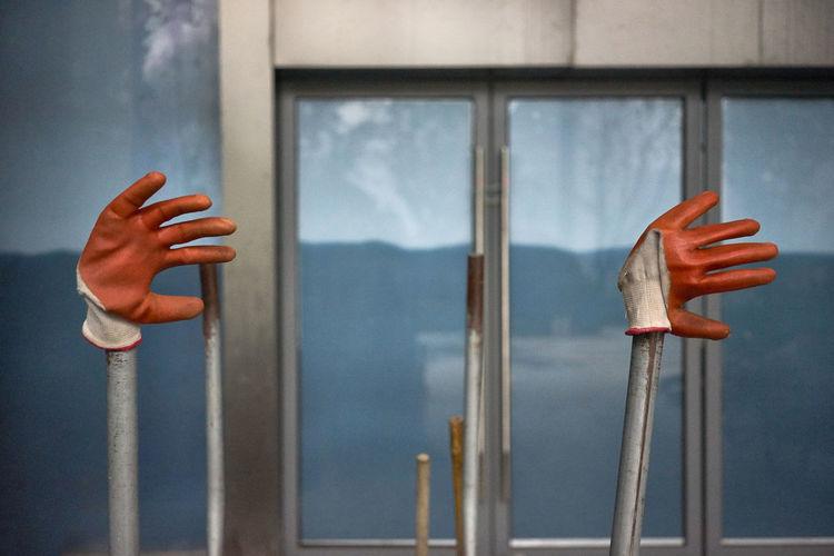 Orange gloves detail on construction site... high five..! Blue Construction Site Five Gloves Highfive Human Hand Orange Outdoors Under Construction Window
