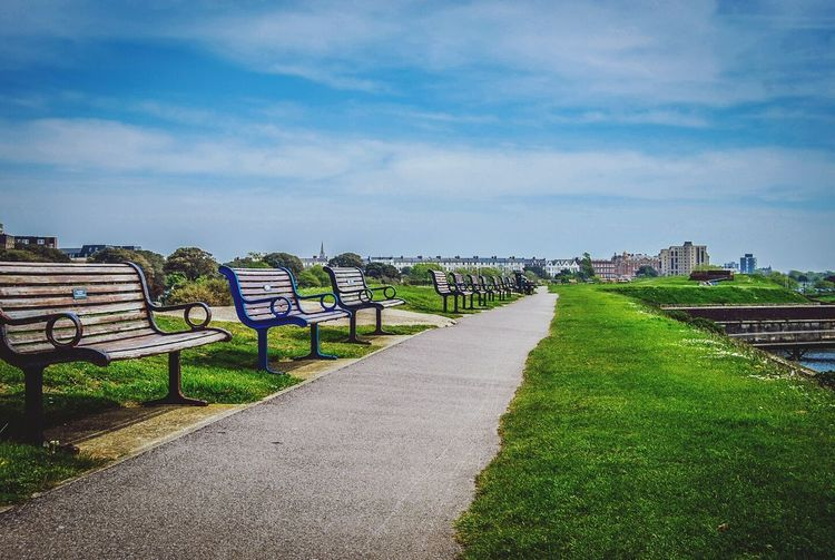 Benches By Walkway In Park Against Cloudy Sky