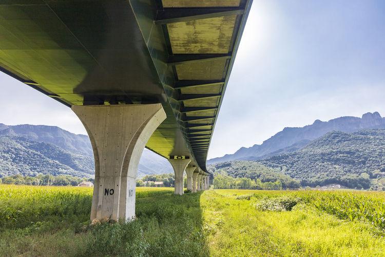 Bridge over field against sky