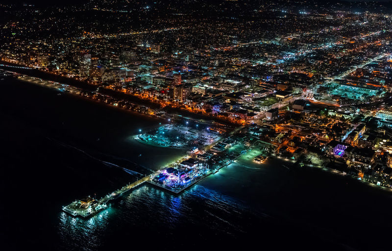 Aerial view of sea by illuminated cityscape at night