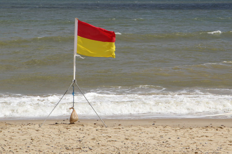 Beach Beach Flags Flag Horizon Over Water No People Safety Flag Sand Sea Surf Warning Warning Flag Water Wave Yellow