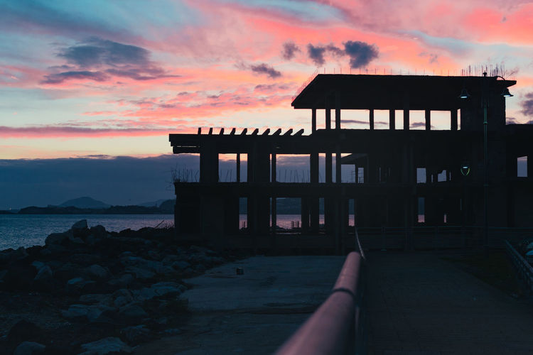 Silhouette built structure on beach against sky during sunset