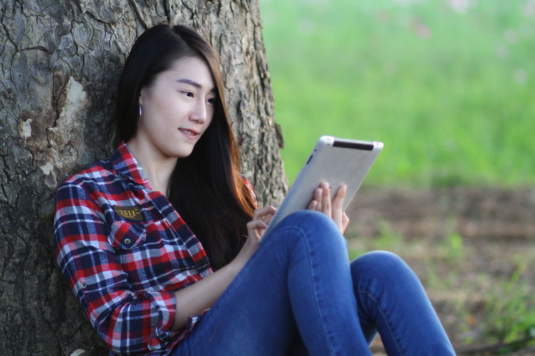 Beautiful woman using digital tablet sitting by tree trunk