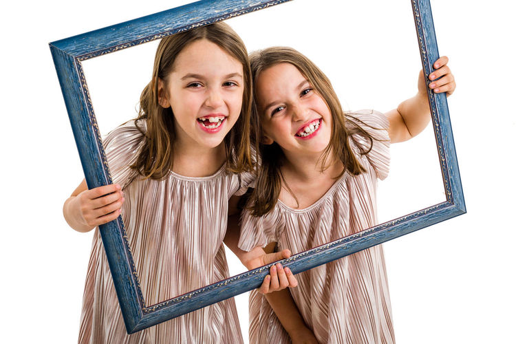 Adorable Background Beautiful Casual Caucasian Cheerful Child Childhood Concept Cute Dress Emotions Empty Expression Face Family Fashion Frame Friendship Fun Girls Hair Happiness Happy Holding Identical  IDENTICAL TWINS Isolated Joyful Kids Laughing Lifestyle Little Looking person Photo Picture Portrait Posing Siblings Sisters Smile Smiling Studio Together Twins Two White Young