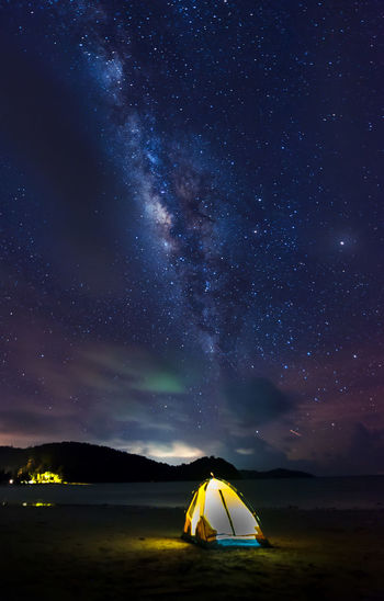 Illuminated Tent On Beach Against Sky At Night