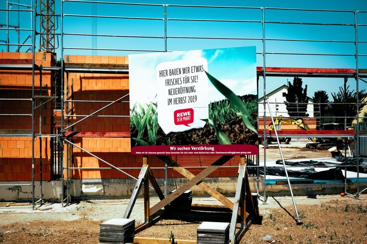 Urban Perspectives Construction Site Street Photography Advertising Billboard Communication Architecture Built Structure Text Sign Day Building Exterior Nature Western Script Railing No People Outdoors Script Non-western Script Wall - Building Feature Sky Information Sunlight